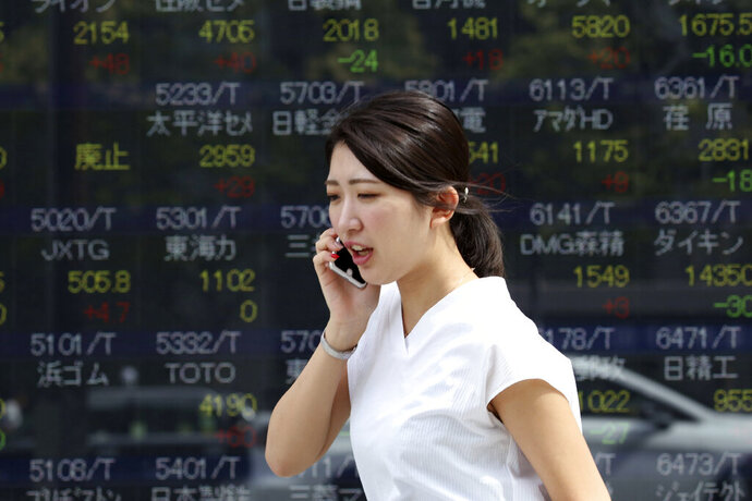 A woman walks by an electronic stock board of a securities firm in Tokyo, Tuesday, Sept. 24, 2019. Shares have edged higher in Asia as U.S. Treasury Secretary Steven Mnuchin confirmed that China-U.S. trade talks were due to resume in two weeks' time. The Shanghai Composite index rose 0.8% and shares also rose in Tokyo and Hong Kong. (AP Photo/Koji Sasahara)