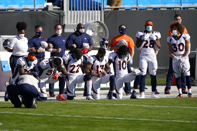 Members of the Denver Broncos kneel during the national anthem before an NFL football game against the Carolina Panthers Sunday, Dec. 13, 2020, in Charlotte, N.C. (AP Photo/Brian Blanco)