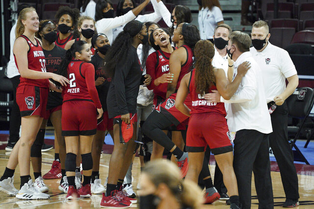 North Carolina State players celebrate with the coaching staff after  an NCAA college basketball game against South Carolina Thursday, Dec. 3, 2020, in Columbia, S.C. (AP Photo/Sean Rayford)