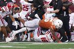 Texas running back Bijan Robinson (5) dives over Louisiana-Lafayette cornerback AJ Washington (16) on a run during the second half of an NCAA college football game Saturday, Sept. 4, 2021, in Austin, Texas. (AP Photo/Eric Gay)