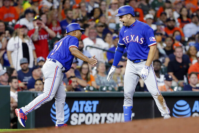 Texas Rangers third base coach Tony Beasley, left, and Nate Lowe, right, celebrate an RBI-triple by Lowe during the fifth inning of a baseball game against the Houston Astros, Friday, July 23, 2021, in Houston. (AP Photo/Michael Wyke)