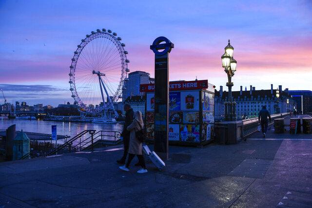 The sun rises over the London Eye, in London, Saturday, Dec. 5, 2020. (AP Photo/Alberto Pezzali)