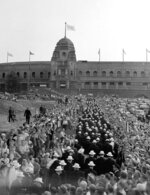 FILE - In this July 29, 1948 file photo,  American contingent pass through the crowd and prepare to enter Wembley Stadium, for the grand parade of all competitors during the opening ceremony of the XIV Summer Olympic Games. London was still cleaning up bombing damage from World War II when it staged the Olympics in 1948. Britain was also struggling financially; food, clothing and gas were still being rationed. The athletes had to bring their own towels and, with housing in short supply, were accommodated in schools and Royal Air Force camps. The games were organized in less than two years, and despite the tiny budget it was a success, its legacies including greater sporting opportunities for women. (AP Photo, File)