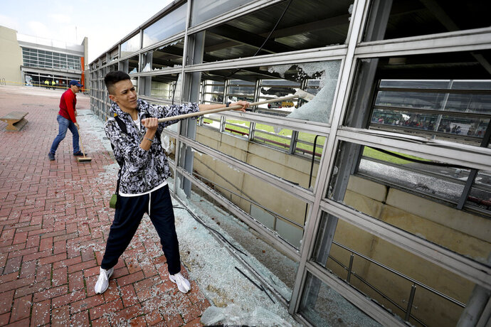 A worker clears broken glass from a bus station damaged by anti-government demonstrators, in Bogota, Colombia, Friday, Nov. 22, 2019. Protesters attacked the station Thursday during a nationwide strike called by labor unions, students and teachers to protest everything from economic inequality to violence against social leaders. (AP Photo/Fernando Vergara)