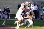 Kansas State quarterback Will Howard (15) is tackled by Oklahoma State safety Tanner McCalister (2) and cornerback Rodarius Williams (8) during the first half of an NCAA college football game in Manhattan, Kan., Saturday, Nov. 7, 2020. (AP Photo/Orlin Wagner)