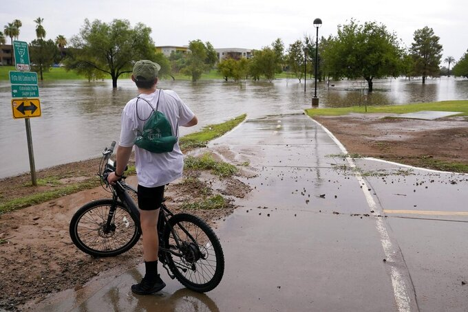 A cyclist is unable to continue his ride as heavy rains caused flooding at Vista del Camino Park, Friday, July 23, 2021, in Scottsdale, Ariz. (AP Photo/Ross D. Franklin)