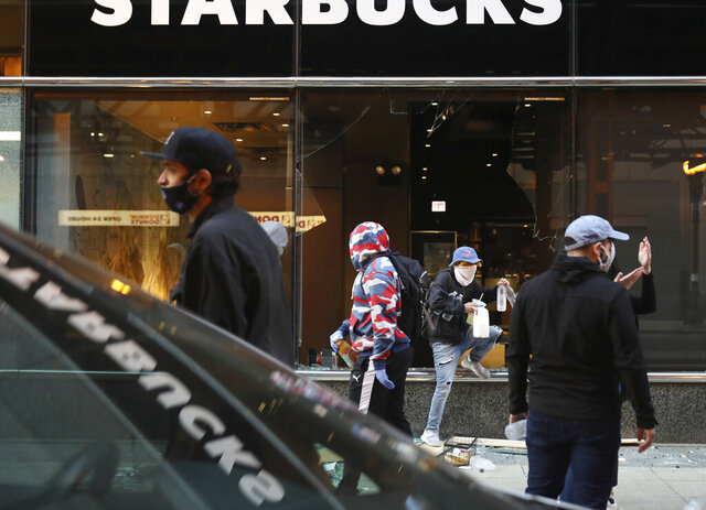 In this Saturday, May 30, 2020 photo, a person exits a broken window of a Starbucks, in Chicago, carrying items after a march and rally over the death of George Floyd. Protests were held in U.S. cities over the death of Floyd, a black man who died after being restrained by Minneapolis police officers on May 25.  (John J. Kim/Chicago Tribune via AP)