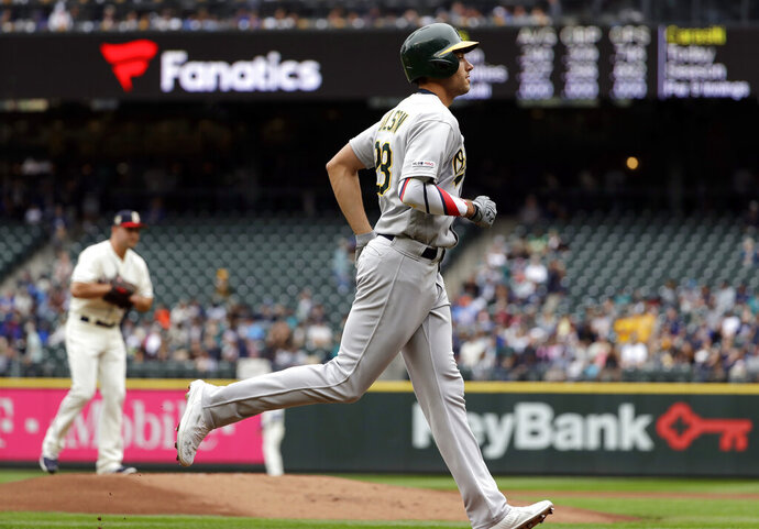 Oakland Athletics' Matt Olson, right, rounds the bases on his three-run home run as Seattle Mariners starting pitcher Matt Carasiti waits for the next batter in the first inning of a baseball game Sunday, July 7, 2019, in Seattle. (AP Photo/Elaine Thompson)