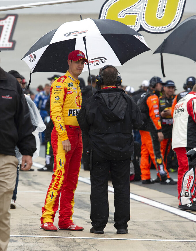 Joey Logano stands on pit road after a NASCAR Cup Series auto race was postponed due to inclement weather conditions Sunday, May 5, 2019, at Dover International Speedway in Dover, Del. (AP Photo/Jason Minto)