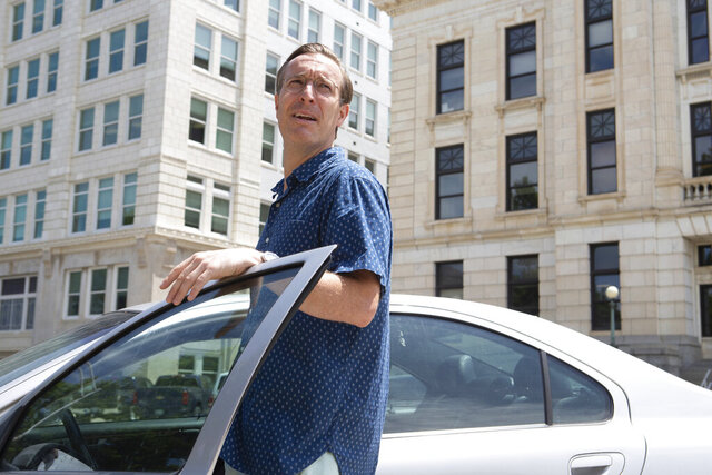 Neil Melton, from Prairie Village, Kan., talks by his car after deciding to leave a rally in opposition to wearing masks due to the small outcome of participants Thursday, July 9, 2020, in Topeka, Kan. (Evert Nelson/The Topeka Capital-Journal via AP)