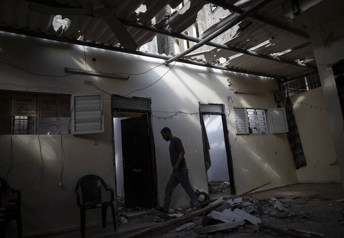 A Palestinian man inspects the damage of his home following Israeli airstrikes on Jabaliya refugee camp, northern Gaza Strip, Thursday, May 20, 2021. Heavy airstrikes pummeled a street in the Jabaliya refugee camp in northern Gaza, destroying ramshackle homes with corrugated metal roofs nearby. The military said it struck two underground launchers in the camp used to fire rockets at Tel Aviv. (AP Photo/Khalil Hamra)