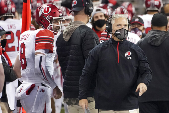 Utah head coach Kyle Whittingham, right, stands near quarterback Jake Bentley (8) during the first half of the team's NCAA college football game against Washington, Saturday, Nov. 28, 2020, in Seattle. (AP Photo/Ted S. Warren)
