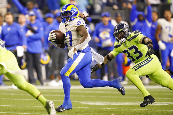 Los Angeles Rams running back Darrell Henderson (27) runs the ball as Seattle Seahawks safety Jamal Adams (33) pursues during the second half of an NFL football game, Thursday, Oct. 7, 2021, in Seattle. (AP Photo/Elaine Thompson)