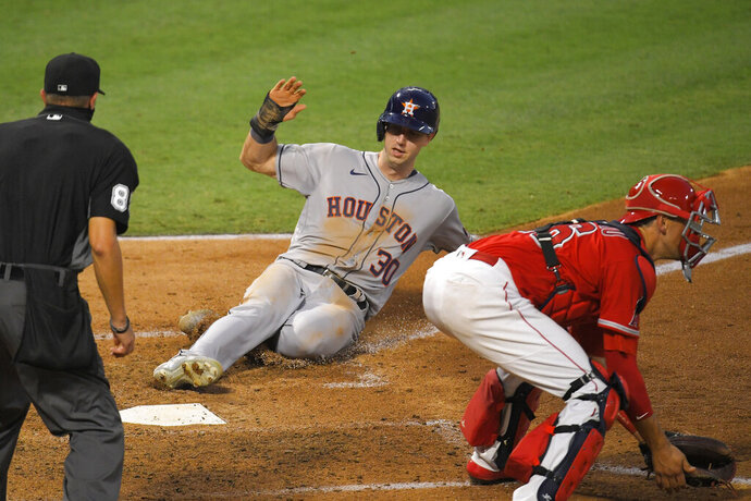 Houston Astros' Kyle Tucker, center, scores on a sacrifice fly by George Springer as Los Angeles Angels catcher Jason Castro, right, takes a late throw and home plate umpire Cory Blaser watches during the fourth inning of a baseball game Friday, July 31, 2020, in Anaheim, Calif. (AP Photo/Mark J. Terrill)
