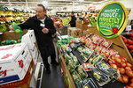 In this Friday, Jan. 18, 2019, photo, assistant produce manager Dave Ruble stocks the imperfect produce section at the Hy-Vee grocery store in Urbandale, Iowa. After enjoying a brief spotlight in supermarket produce sections, blemished fruits and vegetables may already be getting tossed back in the trash. (AP Photo/Charlie Neibergall)