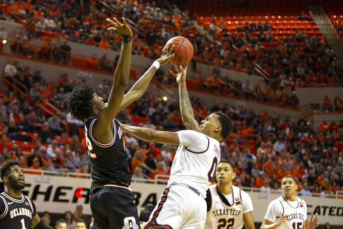 Oklahoma State's Kalib Boone blocks Texas Tech's Kyler Edwards during an NCAA college basketball game in Stillwater, Okla., Saturday, Feb. 15, 2020. (AP Photo/Mitch Alcala)