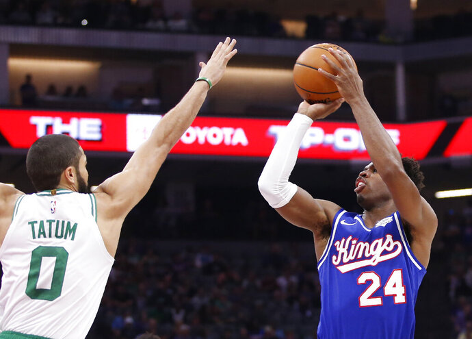 Boston Celtics forward Jayson Tatum, left, challenges the shoot of Sacramento Kings guard Buddy Hield, right, during the first half of an NBA basketball game in Sacramento, Calif., Sunday, Nov. 17, 2019. (AP Photo/Rich Pedroncelli)