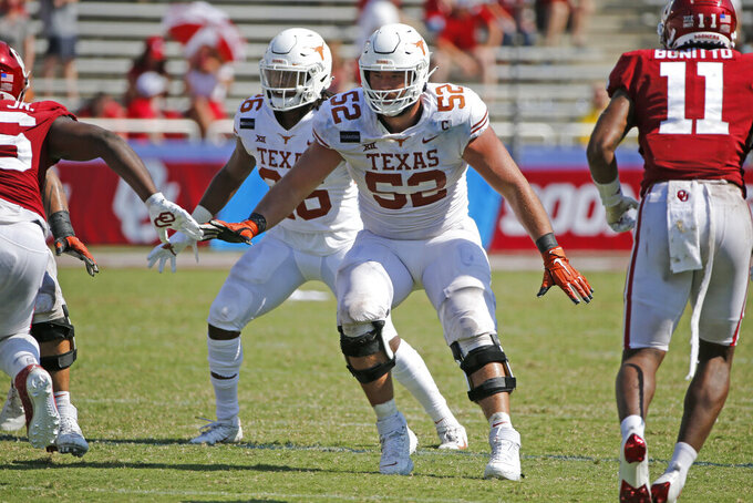 FILE - Texas offensive lineman Samuel Cosmi (52) prepares to block against Oklahoma during the second half of an NCAA college football game in Dallas, Texas, in this Saturday, Oct. 10, 2020, file photo. The Kansas City Chiefs already have spent the offseason rebuilding an offensive line ravaged by injuries and then dominated by Tampa Bay in the Super Bowl. But there is still work to be done, and the next opportunity to provide some help up front for quarterback Patrick Mahomes is the NFL draft. (AP Photo/Michael Ainsworth, File)