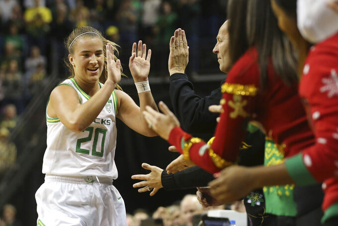 Oregon's Sabrina Ionescu, left, is congratulated by head women coach Kelly Graves and others on the bench after recording her 21st career triple double in an NCAA college basketball game against Kansas State in Eugene, Ore., Saturday, Dec. 21, 2019. (AP Photo/Chris Pietsch)