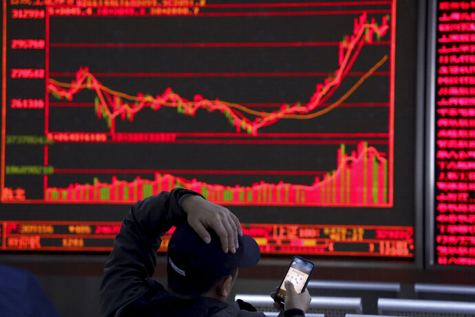 An investor plays a mobile chess game while watching stock prices at a brokerage in Beijing, China, Tuesday, March 19, 2019. Asian shares are mixed in muted trading as investors await the U.S. Federal Reserve meeting later in the week.   (AP Photo/Ng Han Guan)