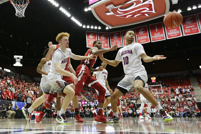 Arizona guard Nico Mannion, left, and guard Jemarl Baker Jr., right, and Washington State guard Marvin Cannon go after the ball during the second half of an NCAA college basketball game in Pullman, Wash., Saturday, Feb. 1, 2020. Arizona won 66-49. (AP Photo/Young Kwak)