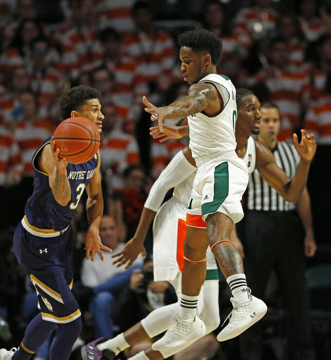 Notre Dame guard Prentiss Hubb (3) looks to pass against Miami guard Chris Lykes (0) during the second half of an NCAA college basketball game, Wednesday, Feb. 6, 2019 in Coral Gables, Fla. (David Santiago/Miami Herald via AP)