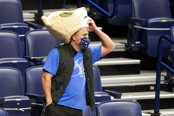 A Kentucky fan watches the final moments of the second half during a loss to Mississippi State in an NCAA college basketball game in the Southeastern Conference Tournament Thursday, March 11, 2021, in Nashville, Tenn. (AP Photo/Mark Humphrey)