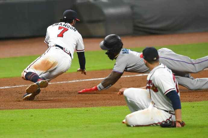 Atlanta Braves shortstop Dansby Swanson (7) moves in to tag out Miami Marlins' Monte Harrison, back right, at third base for a double play on a throw from first baseman Freddie Freeman as Braves relief pitcher Mark Melancon ducks in the foreground during the ninth inning of a baseball game Monday, Sept. 21, 2020, in Atlanta. (AP Photo/John Amis)