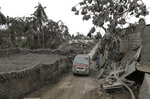 A vehicle navigates the volcanic ash covered village in Talisay, Batangas province, southern Philippines on Wednesday Jan. 15, 2020. Taal volcano is spewing lava into the sky and trembled constantly, possibly portending a bigger and more dangerous eruption, as tens of thousands of people fled villages darkened and blanketed by heavy ash. (AP Photo/Aaron Favila)