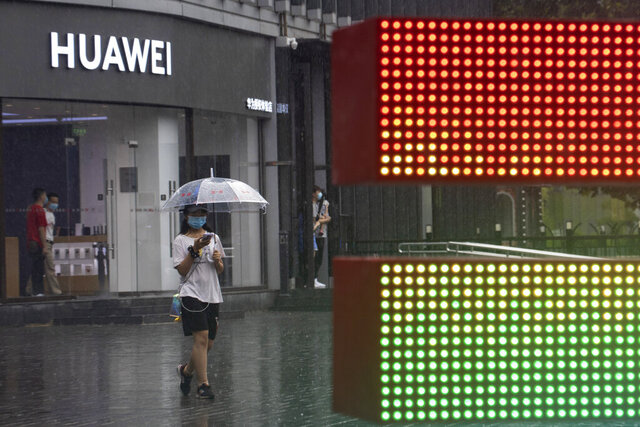 A woman wearing a mask to protect from the coronavirus walks with an umbrella as it rains outside a Huawei store in Beijing on Wednesday, Aug. 5, 2020. For nearly a decade, Huawei kept worldwide sales growing as Washington told U.S. phone companies not to buy its network equipment and lobbied allies to reject China's first global tech brand as a security threat. (AP Photo/Ng Han Guan)