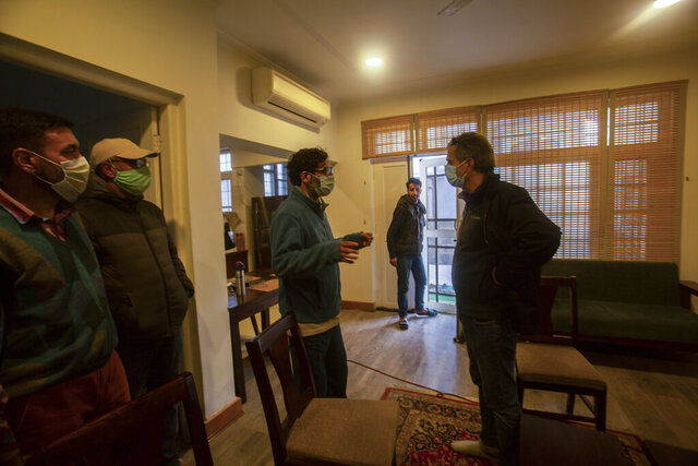 Agence France-Presse's Kashmir correspondent Parvaiz Bukhari, centre, talks to his colleagues after National Investigation Agency personnel searched his premises on the outskirts of Srinagar, Indian controlled Kashmir, Wednesday, Oct. 28, 2020. (AP Photo/Mukhtar Khan)
