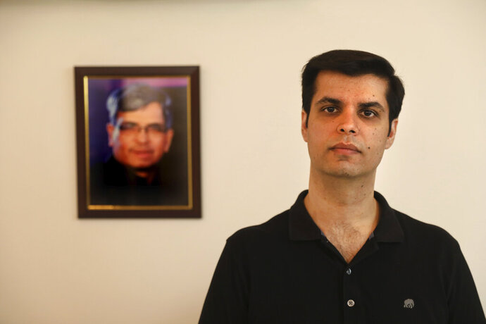 Karan Murgai, an IT management consultant for a multinational based in Dallas, poses for a photograph next to then portrait of his father Satish Murgai, in his Delhi house, in New Delhi, India, Tuesday, June 30, 2020. Murgai came to Delhi in March this year after his father died. Murgai and at least 1,000 others like him, whose U.S. visas are tied to their jobs in the U.S., are now stranded in India, after an executive order signed by President Donald Trump that suspends applications for H-1B and other high-skilled work visas from abroad. (AP Photo/Manish Swarup)