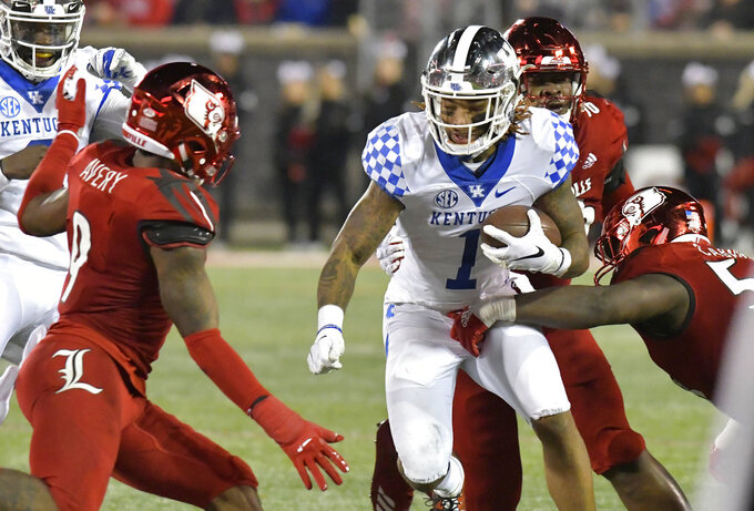Kentucky wide receiver Lynn Bowden Jr. (1) is wrapped up by Louisville defensive end Amonte Caban (53) during the second half of an NCAA college football game in Louisville, Ky., Saturday, Nov. 24, 2018. Louisville won 56-10. (AP Photo/Timothy D. Easley)