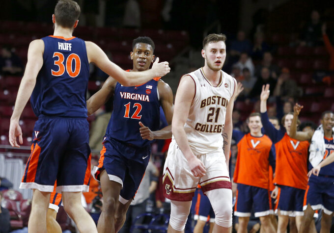 Virginia forward Jay Huff (30) and guard De'Andre Hunter (12) celebrate a 3-point basket as Boston College forward Nik Popovic (21) walks past during the second half of an NCAA basketball game Wednesday, Jan. 9, 2019, in Boston. (AP Photo/Mary Schwalm)