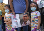 """A Palestinian man holds a poster showing Mahmoud Nawajaa, a leading coordinator of the Palestinian-led boycott movement against Israel, BDS, during a protest calling for the EU to press for his release, in front of the German Representative Office, in the West Bank city of Ramallah, Tuesday, Aug. 11, 2020. The activist was arrested on July 30, remains in Israeli custody and has not been charged. Israel says the arrest is not connected to his boycott activities, and that he is is suspected of unspecified """"security offenses,"""