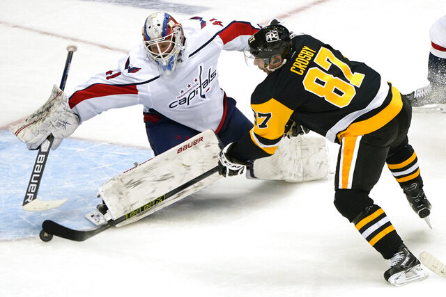 Pittsburgh Penguins' Sidney Crosby (87) gets a shot past Washington Capitals goaltender Vitek Vanecek (41) for an overtime goal in an NHL hockey game in Pittsburgh, Tuesday, Jan. 19, 2021. The Penguins won 5-4. (AP Photo/Gene J. Puskar)