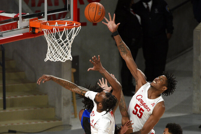 Houston forward Brison Gresham (55) and guard DeJon Jarreau, left, go for a rebound during the first half of the team's NCAA college basketball game against Tulsa, Wednesday, Jan. 20, 2021, in Houston. (AP Photo/Eric Christian Smith)