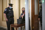 FILE - In this Jan. 12, 2021, file photo, Rep. Marjorie Taylor Greene, R-Ga., passes through a metal detector before entering the House chamber, a new security measure put into place after a mob stormed the Capitol, in Washington.  Republicans have a Marjorie Taylor Greene problem. Again. Before she joined Congress this month, Greene supported Facebook posts that advocated violence against leading Democrats and the FBI. While some Republicans condemned the activity on Wednesday, it was hardly a surprise. Facebook posts surfaced last year showing she'd expressed racist, anti-Semitic and anti-Muslim views.  (AP Photo/J. Scott Applewhite, File)