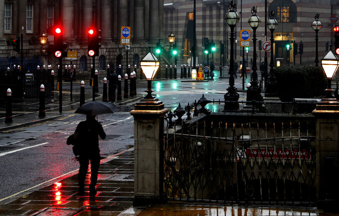 A man with an umbrella walks through a street in the financial area of London, Wednesday, Jan. 13, 2021 during England's third national lockdown to curb the spread of coronavirus. (AP Photo/Alastair Grant)