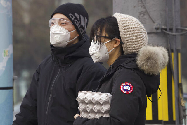 Residents wearing masks wait at a traffic light in Beijing, China Thursday, Feb. 13, 2020. China is struggling to restart its economy after the annual Lunar New Year holiday was extended to try to keep people home and contain novel coronavirus. Traffic remained light in Beijing, and many people were still working at home. (AP Photo/Ng Han Guan)