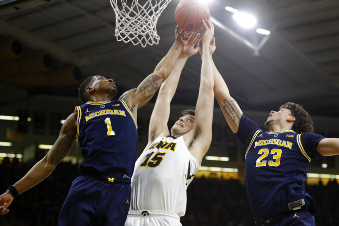Iowa forward Ryan Kriener, center, fights for a rebound with Michigan's Charles Matthews, left, and Brandon Johns Jr. during the first half of an NCAA college basketball game Friday, Feb. 1, 2019, in Iowa City, Iowa. (AP Photo/Charlie Neibergall)