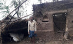 This photo provided by the Indian Red Cross Society shows a villager standing outside his damaged house after Cyclone Amphan, the equivalent of a category 3 hurricane, hit the area in Bhadrak district of Orissa state, India, Thursday, May 21, 2020. A powerful cyclone ripped through densely populated coastal India and Bangladesh, blowing off roofs and whipping up waves that swallowed embankments and bridges and left entire villages without access to fresh water, electricity and communications. At least 24 people were reported killed Thursday. (Indian Red Cross Society via AP)