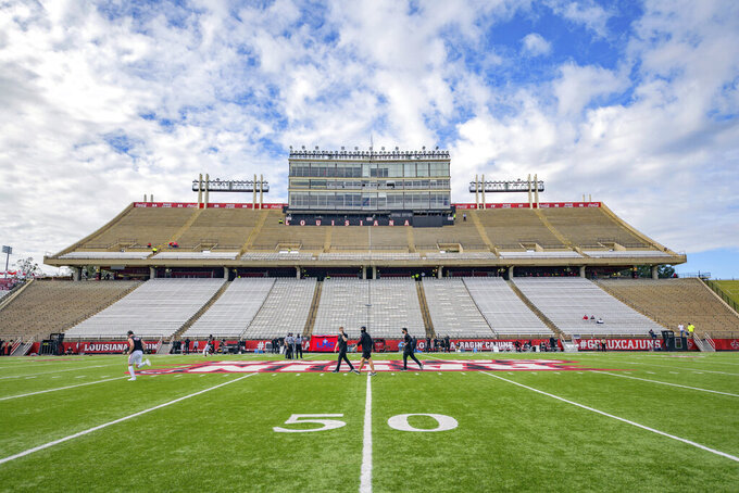 """FILE - Teams warm up on Cajun Field before an NCAA college football game between Louisiana-Lafayette and Arkansas State in Lafayette, La., in this Saturday, Nov. 7, 2020, file photo. Louisiana-Lafayette's Cajun Field will undergo $15 million in renovations and improvements because of a local hospital's decision to provide the largest philanthropic gift in the history of the Ragin' Cajuns athletic department. Our Lady of Lourdes Medical Center will receive naming rights in exchange for what ULL Athletic Director Bryan Maggard described as a """"transformational gift"""" this week. (AP Photo/Matthew Hinton, File)"""