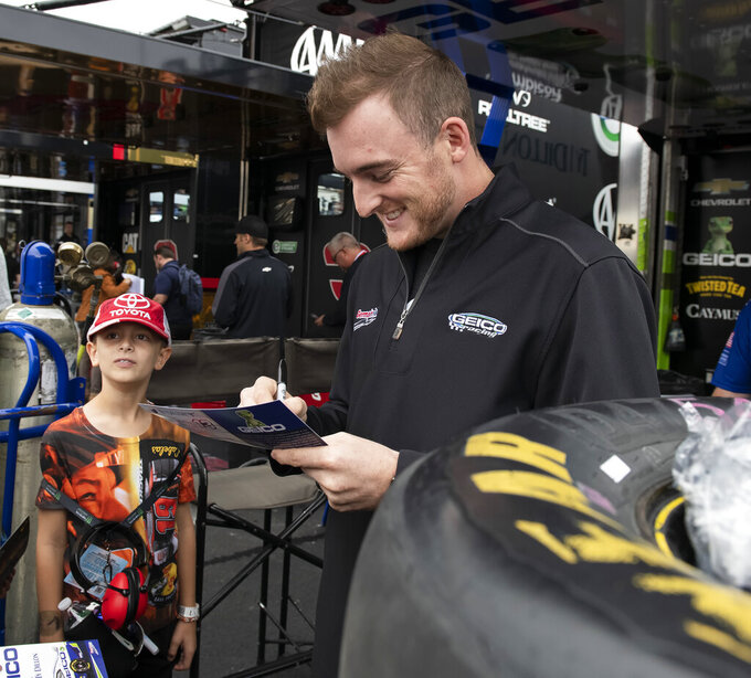 Ty Dillon, right, gives autographs before the Drydene 400 - Monster Energy NASCAR Cup Series playoff auto race, Sunday, Oct. 6, 2019, at Dover International Speedway in Dover, Del. (AP Photo/Jason Minto)