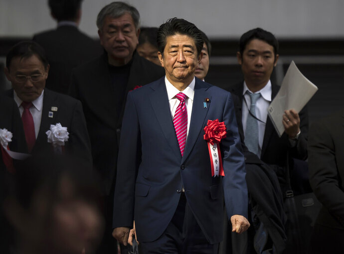 FILE - In this Dec. 15, 2019, file photo, Japan's Prime Minister Shinzo Abe arrives for the construction completion ceremony of the New National Stadium, the venue for next year's opening and closing ceremony of the Tokyo Olympics and track and field in Tokyo, Japan. In a meeting Monday, Feb. 3, 2020, with the national legislature, Abe reassured them that the Summer Olympics will be taking place on schedule despite rumors of it being affected by the current coronavirus outbreak. (Tomohiro Ohsumi/Pool Photo via AP)