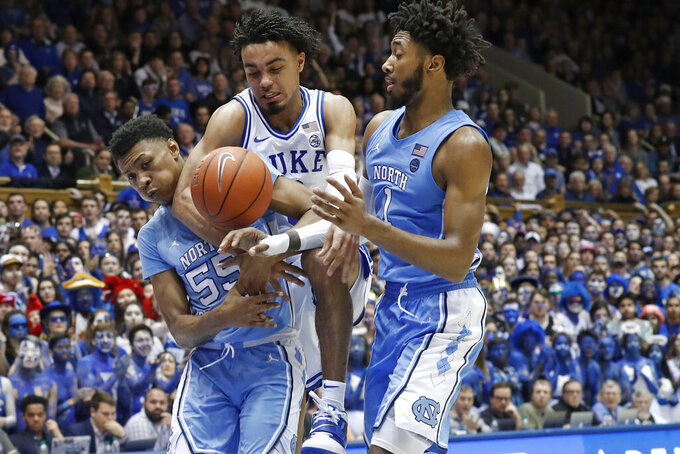 Duke guard Tre Jones drives between North Carolina guard Christian Keeling (55) and guard Leaky Black during the second half of an NCAA college basketball game in Durham, N.C., Saturday, March 7, 2020. (AP Photo/Gerry Broome)
