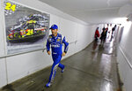 FILE - In this April 19, 2015 file photo, NASCAR driver Jimmie Johnson runs through the tunnel during a rain delay in a Sprint Cup Series auto race at Bristol Motor Speedway in Bristol, Tenn. Johnson plans to run in the Boston Marathon on Monday, April 15, 2019. (AP Photo/Wade Payne, File)