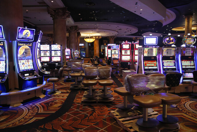 Chairs sit on pallets as some are being removed from electronic slot machines to maintain social distancing between players at a closed Caesars Palace hotel and casino Thursday, May 21, 2020, in Las Vegas. Casino operators in Las Vegas are awaiting word when they will be able to reopen after a shutdown during the coronavirus outbreak. (AP Photo/John Locher)