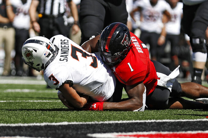 FILE - In this Oct. 5, 2019, file photo, Texas Tech's Jordyn Brooks (1) tackles Oklahoma State's Spencer Sanders (3) to stop a 2-point-conversion attempt during the second half of an NCAA college football game in Lubbock, Texas. The Seattle Seahawks selected Brooks in the first round of the NFL draft Thursday, April 23, 2020. (AP Photo/Brad Tollefson, File)