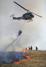 Cal Fire's Boggs helitack crew from Cobb Mountain, Calif.,  assist in putting out a 12 acre brush fire in Larkfield Calif., Thursday, Sept. 24, 2020  (Kent Porter/The Press Democrat via AP)
